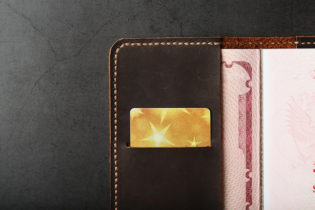 Open passport leather cover with gold credit card