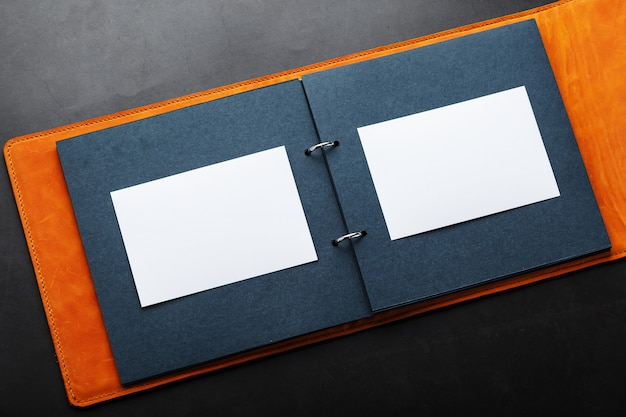 Open photo album with empty space for photos, white frames on black paper. the album cover is made of brown handmade genuine leather