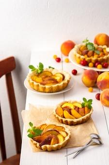 Открытый пирог из песочного теста с персиками, персиковыми клафути на белом столе
