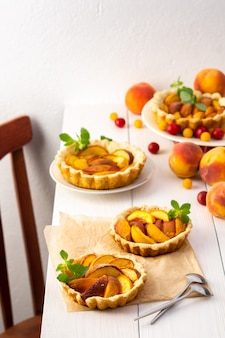 Open pie from shortcrust pastry with peaches, peach clafoutis on white table