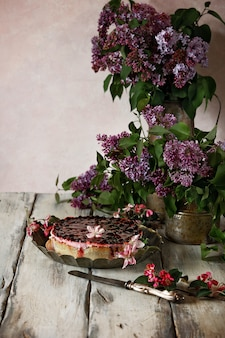 Open pie with berry jelly and berries on a vintage dish. still life with branches of lilac