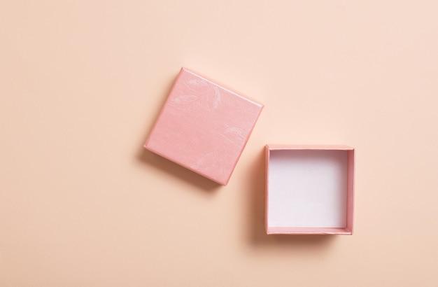 パステル紙の背景にピンクのボックスを開く