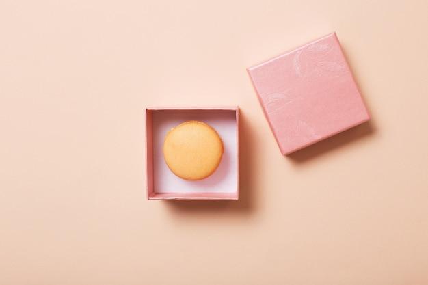 Открытая розовая коробка с макарунами на фоне бумаги в пастельных тонах