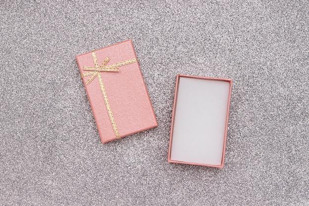 Открытая розовая подарочная коробка с бантом на серебряном блестящем фоне в минималистском стиле
