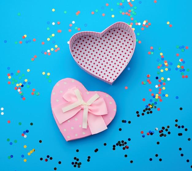 Открытая розовая сердцевидная картонная коробка на синем фоне с разноцветным блестящим конфетти