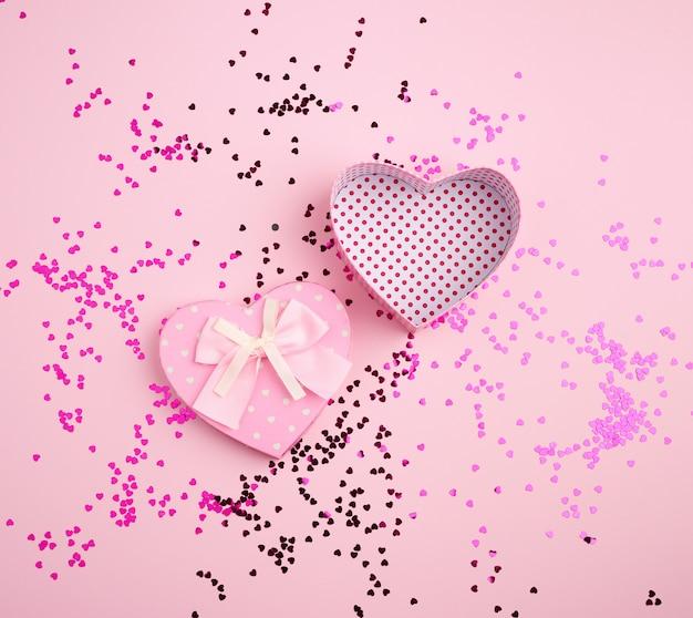 Открытая розовая сердцевидная картонная коробка на розовом фоне с разноцветным блестящим конфетти