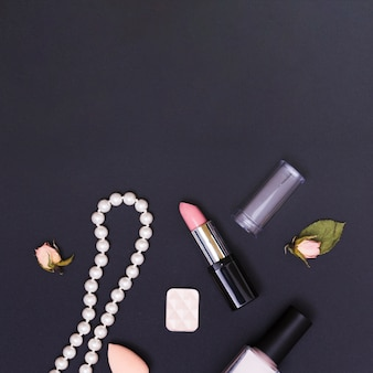 An open pink lipstick; nail polish; necklace; sponge; rose bud and eyeshadow on black background