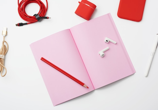Open pink paper notebook, cable, red smartphone, headphones on white background, workplace, top view, flat lay