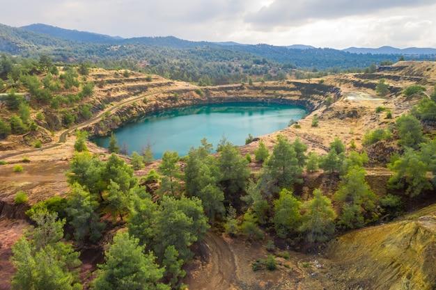 오래된 폐기물 덤프 위에 복원된 숲이 있는 kapedes cyprus 근처의 노천 구리 광산 지역