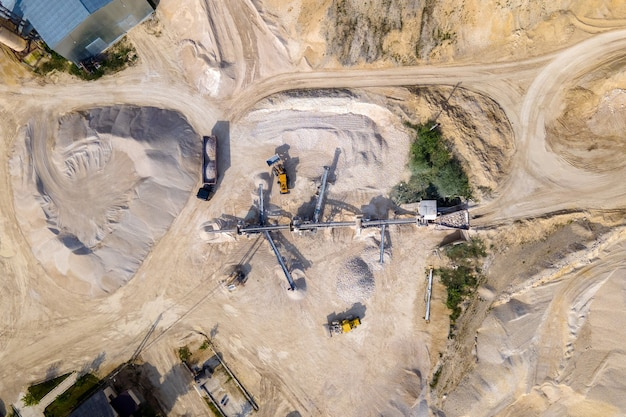 Open pit mining of construction sand stone materials with excavators and dump trucks at conveyor belt.