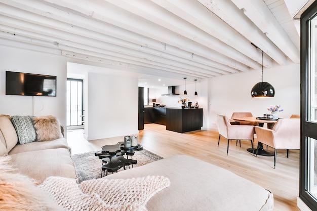 식탁과 회색 소파가있는 흰색 거실의 오픈 플랜 블랙 주방