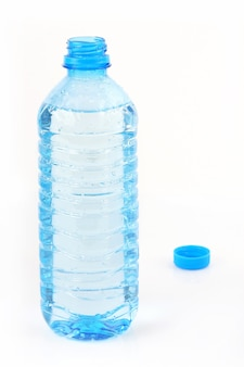 Open plastic bottle with water and cup behind