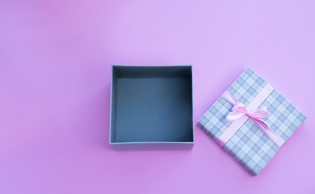 Open present box with pink bow  on pink background