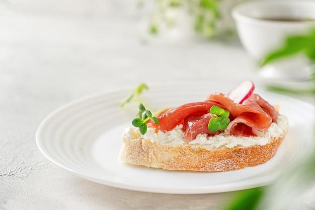 Open prosciutto sandwich with cream cheese, radish and microgreens