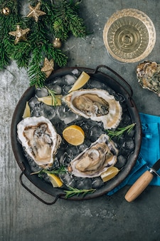 Open raw oysters with lemon and rosemary. fresh seafood on a metal tray top view. christmas concept
