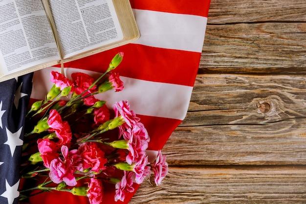 アメリカの国旗の切り花のカーネーションのクローズアップに聖書を読む