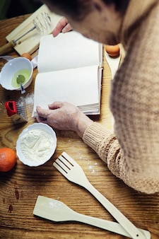 Open recipe book in the hands of an elderly woman in front of a table with utensils
