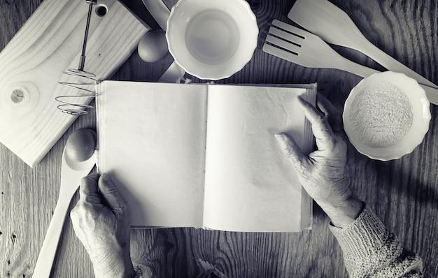 Открытая книга рецептов в руках пожилой женщины перед столом с посудой
