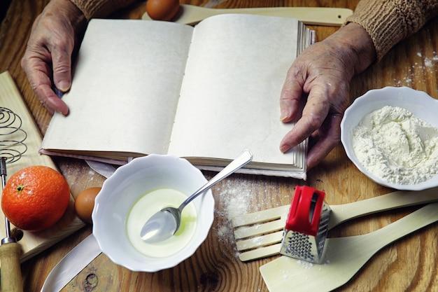 기구가 있는 탁자 앞에 있는 노부인의 손에 있는 요리책 열기