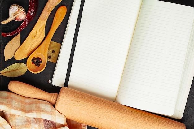 Открытая книга рецептов, скалка, нож, ложка и специи на старом темном столе