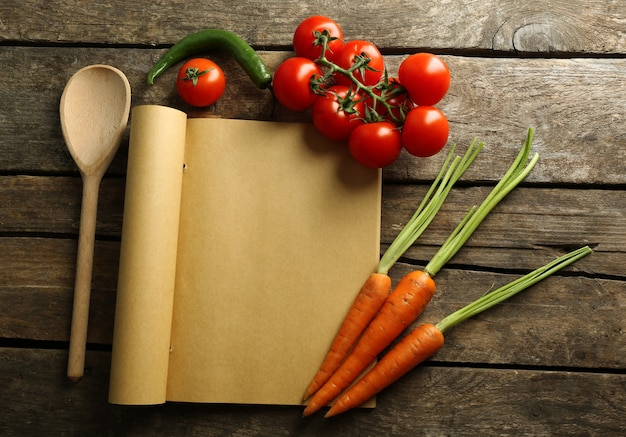 Open recipe book, vegetables and spices on wooden background