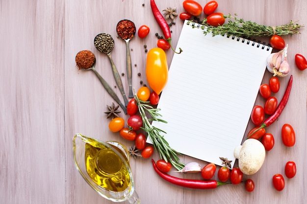 新鮮なハーブ、トマト、スパイスを木製のテーブルで開いているレシピ本