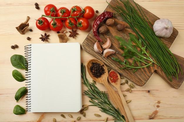 Открытая книга рецептов со свежими травами, помидорами и специями на деревянном