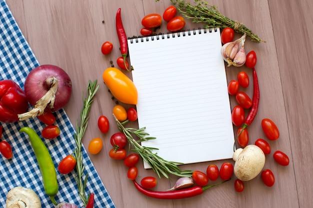Открытая книга рецептов со свежими овощами и зеленью на деревянном столе