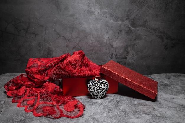 Откройте красную коробку с торчащей красной тканью и пустым деревянным сердечком, выкрашенным в белый цвет.
