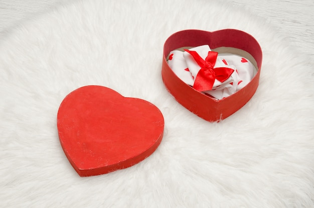 Open red box with heart shaped linen, white fur. top view
