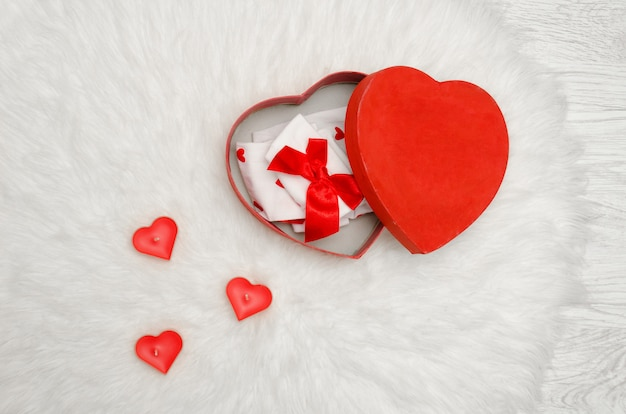 Open red box with heart shaped red and white linen on a white fur. candles in the shape of a heart, a top view