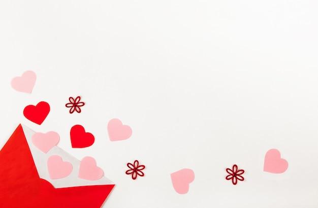 많은 다른 빨간색과 분홍색 하트가 나오는 빨간 봉투를 열고 연애 편지로 흰색 배경 위에 퍼졌습니다. 발렌타인 데이 개념. 평면도, 평면 배치