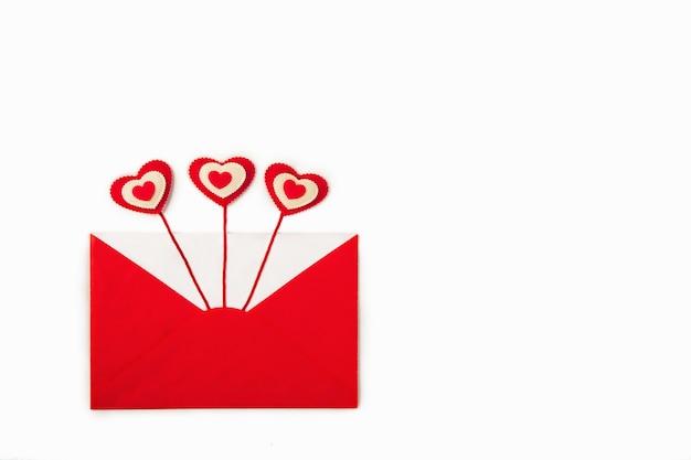 Открытый красный конверт с тремя красными сердечками выходит как любовное письмо.
