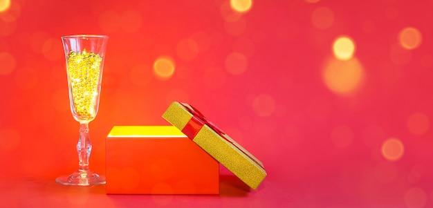 Открытая красная подарочная коробка и бокал шампанского с пузырьковыми бусинами