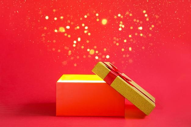 Открытая красная подарочная коробка с золотым сиянием и блеском внутри на красном фоне