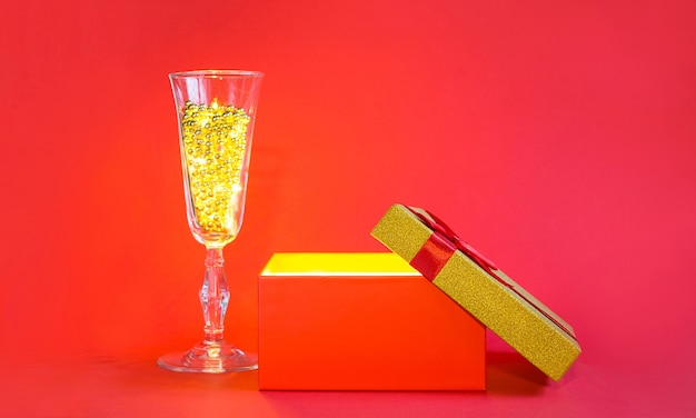 金色の輝きと泡ビーズとシャンパングラスで赤いギフトボックスを開きます