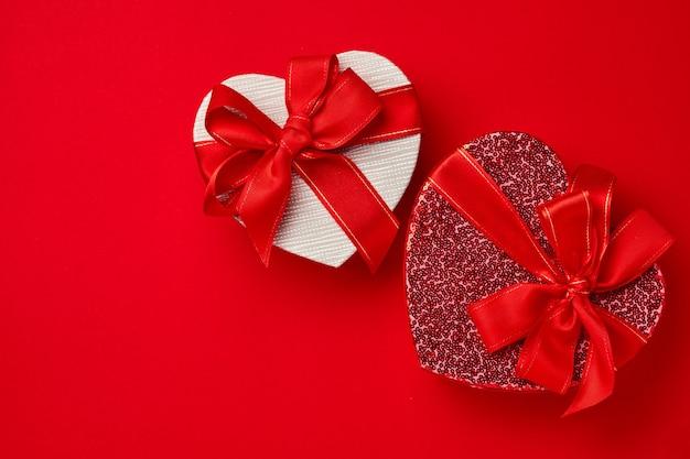 붉은 심장 상자, 리본, 그리고 주홍 배경 근처에 흩어져 있는 하트를 엽니다. 발렌타인 데이 엽서 또는 개념입니다. 텍스트를 위한 공간입니다. 평면도.