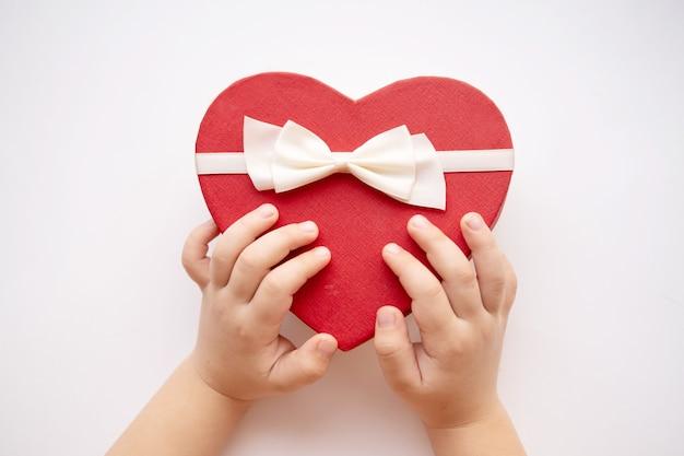 아기 손으로 흰색에 흰색 리본 레드 하트 선물 상자를 엽니 다.