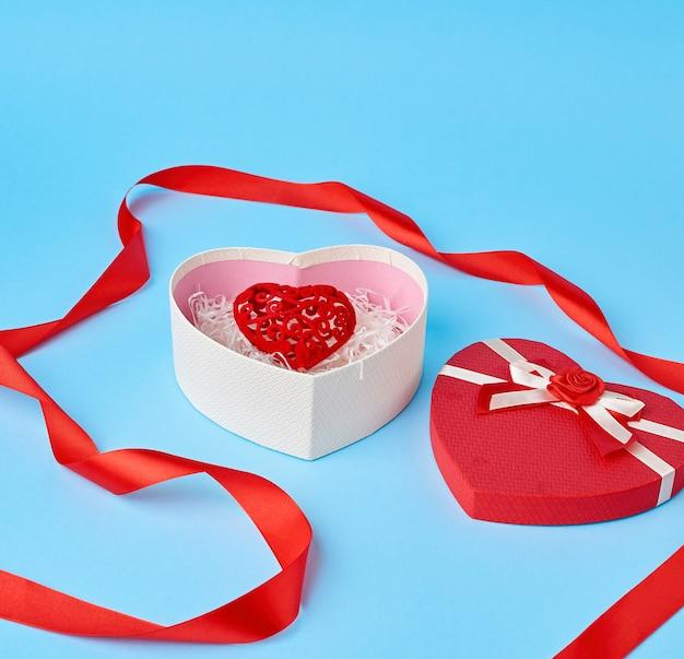 Открытая красная подарочная коробка в форме сердца с бантиком на синем