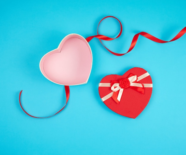 Open red heart-shaped gift box with a bow on a blue background