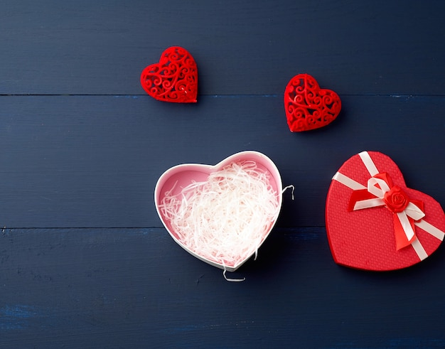 Open red heart-shaped gift box with a bow on a blue wooden