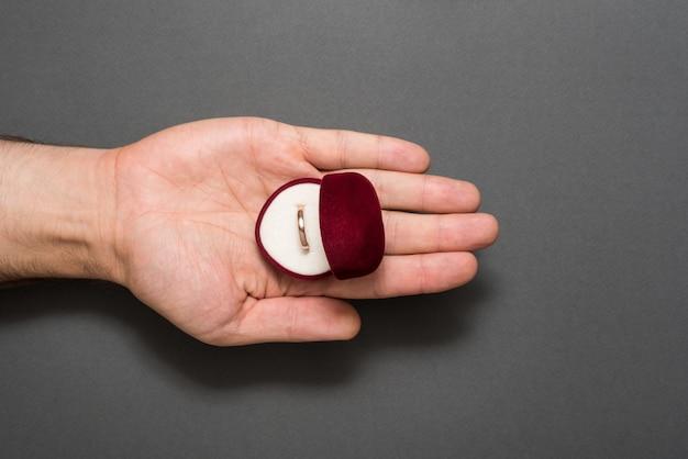 男性の手のひらに婚約指輪の開いた赤い宝石箱。プレゼント。