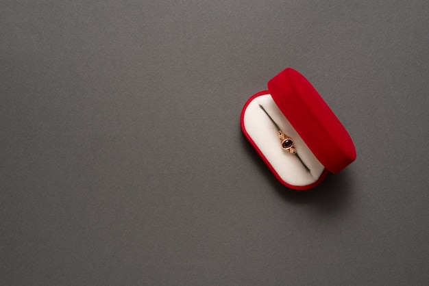Open red jewelry box with jewelry on a black background.