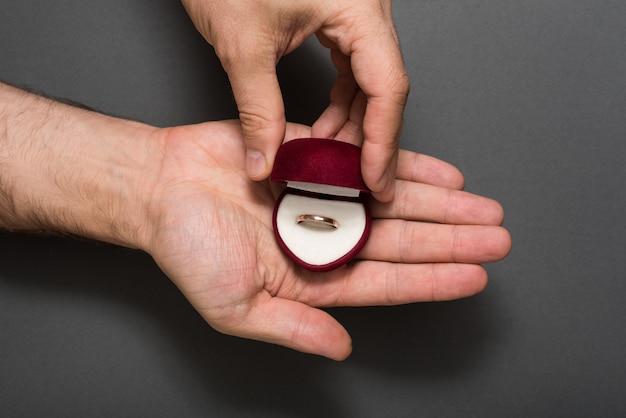 男性の手にリングで赤い宝石箱を開きます。プレゼント。