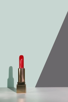 Open red lipstick with his shadow on grey and brown background