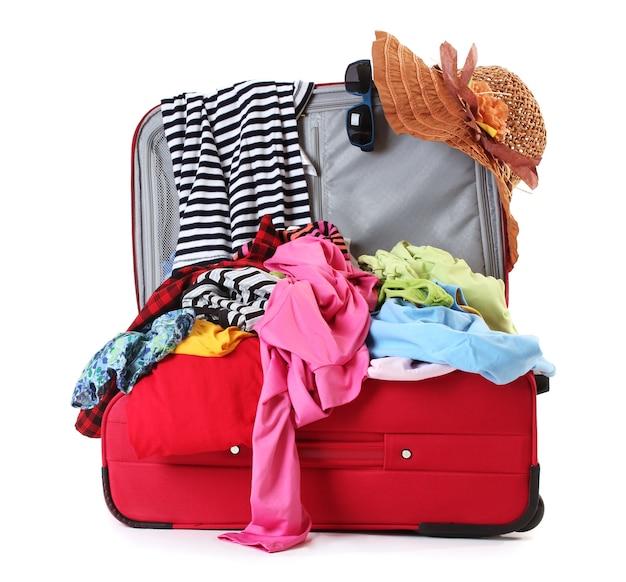 白で隔離される服で赤いスーツケースを開く