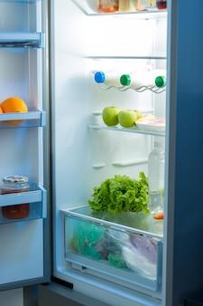 夜のキッチンで食べ物でいっぱいの冷蔵庫を開く Premium写真