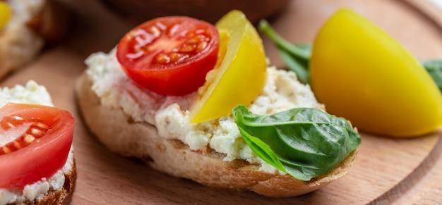 Открытый сэндвич с помидорами, мягким сыром, базиликом. вкусный завтрак или закуска, чистое питание, диета, концепция веганского питания. вид сверху.