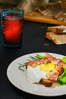 하얀 접시에 호밀 사워 도우 빵 한 조각에 베이컨, 튀긴 계란, 셀러리 잎이 달린 오픈 샌드위치