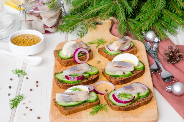 Open sandwich with rye bread, fresh cucumber, pickled onions, herring and dill.  appetizer for new year and christmas.